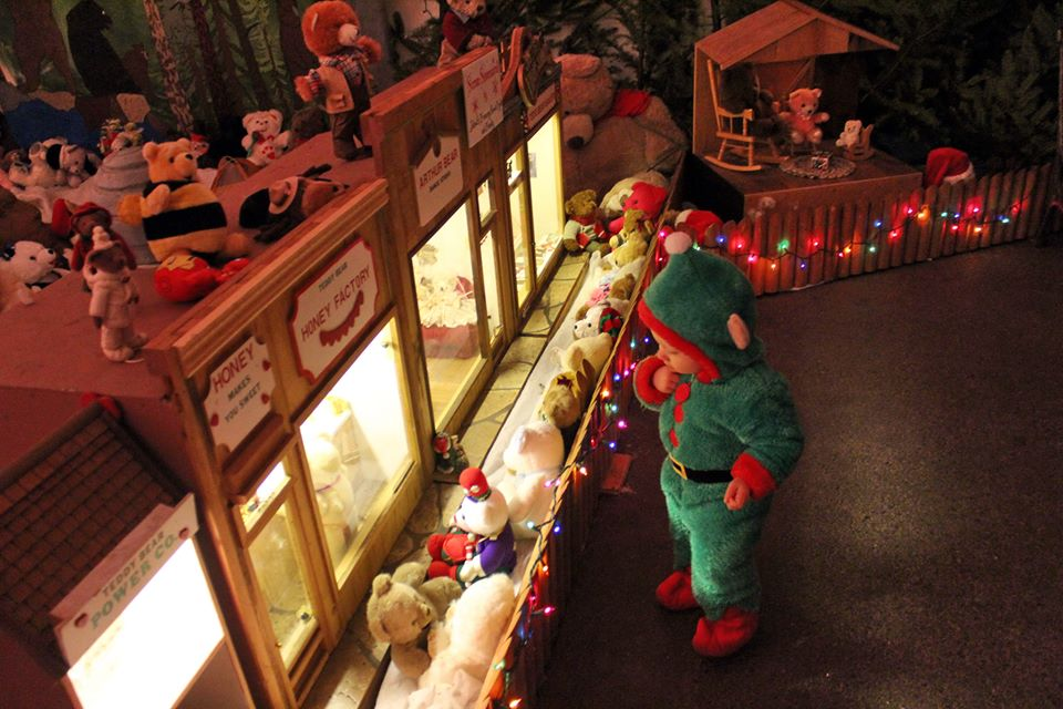 Child in elf costume entranced by Christmas display.