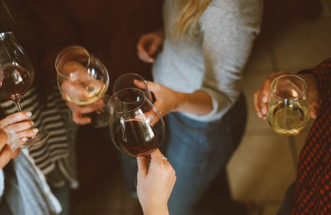 Photo of people holding full wine glasses.
