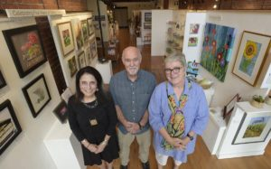 Photo of artists standing inside the Gallery Calapooia where their art is displayed.