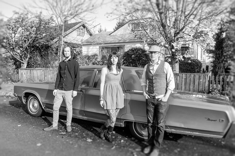 Photo three people in front of old car.