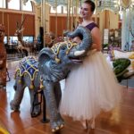 Ballet dancer in costume with Carousel baby elephant.