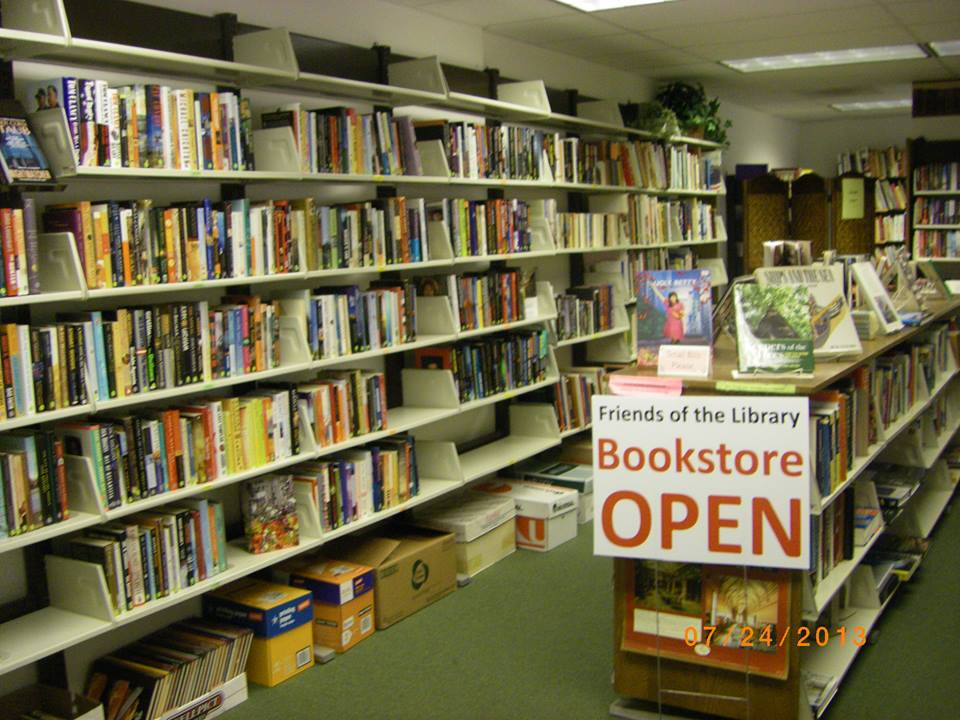 "Photo of crowded book shelves with sign reading ""Open."""
