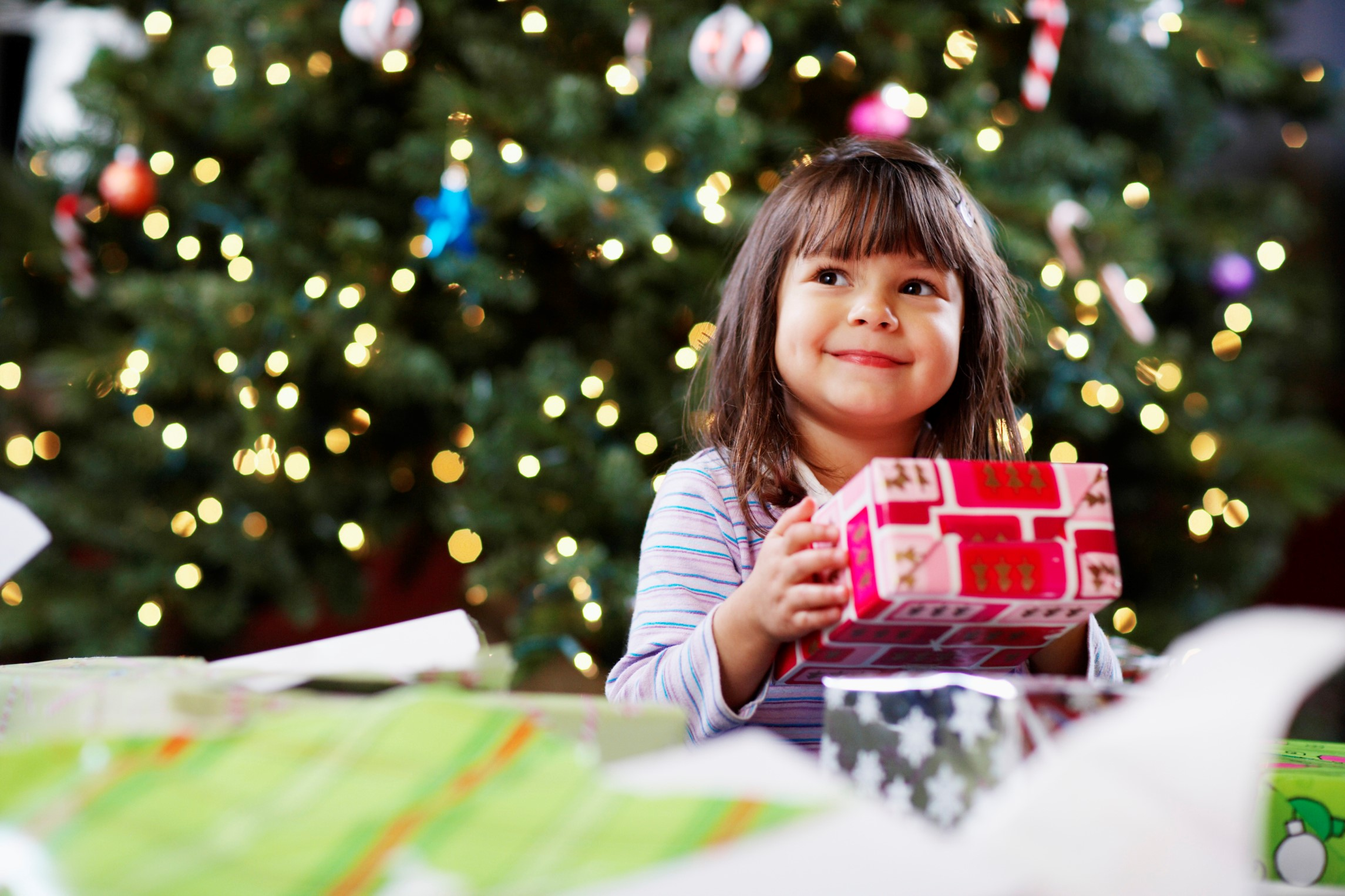 Photo of little girl smiling with gift in hand and Christmas tree in background.
