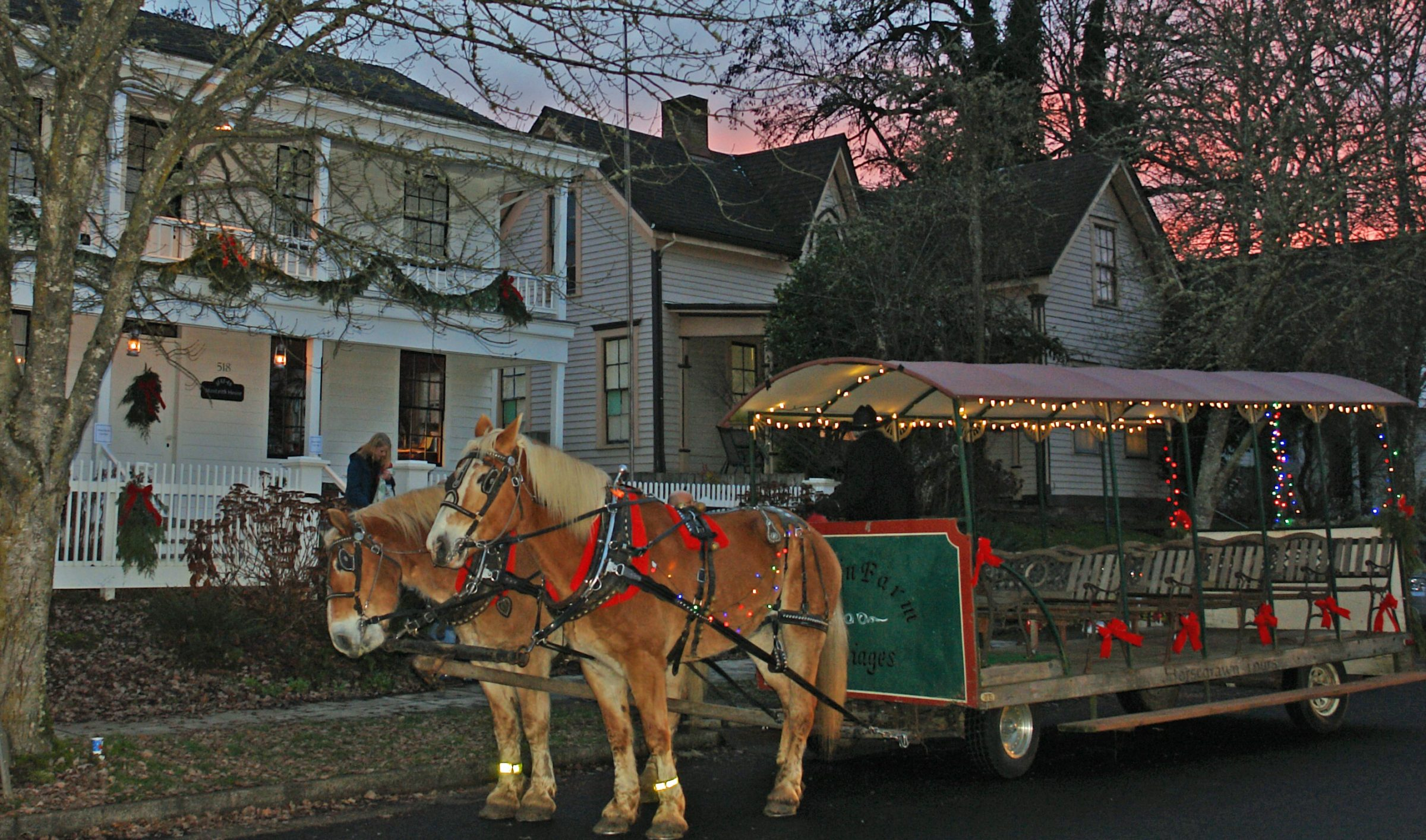 Photo of horses with wagon in front of historic house decorated for Christmas.