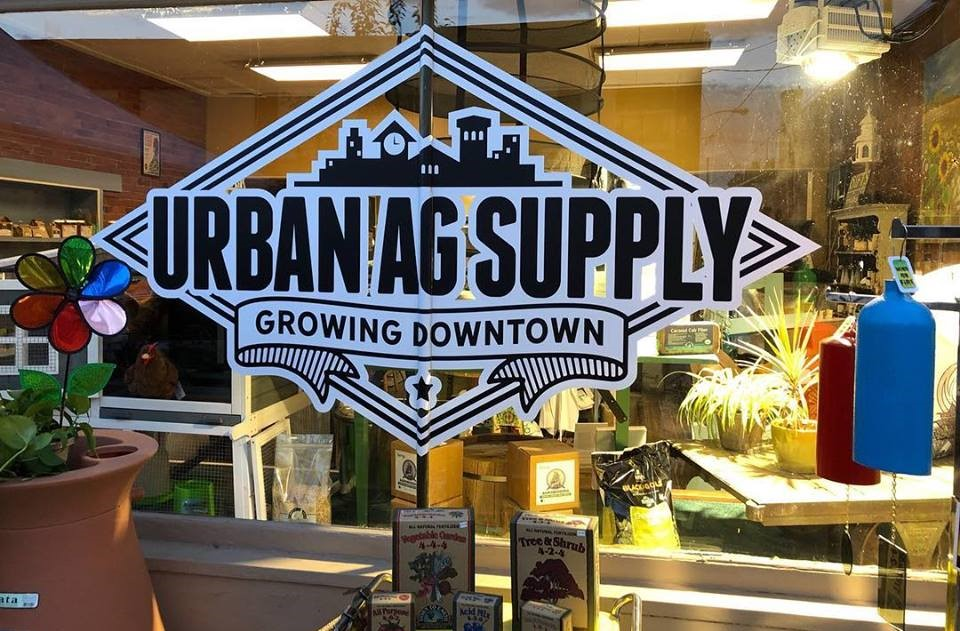 "Photo of shop window with logo ""Urban Ag Supply - Growing Downtown."""