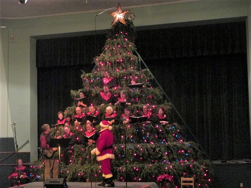 Photo of choir in large tree with Santa.