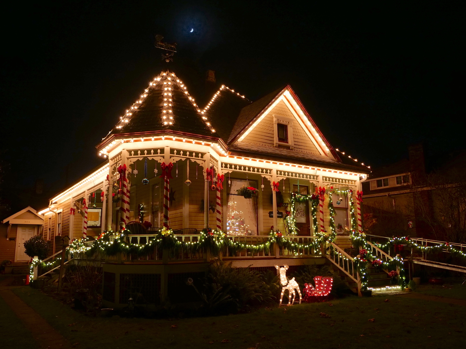 photo of a historic Victorian period house at night, lit with Christmas lights and lighted yard decorations for the 2018 Albany Oregon Night Time Magic Program