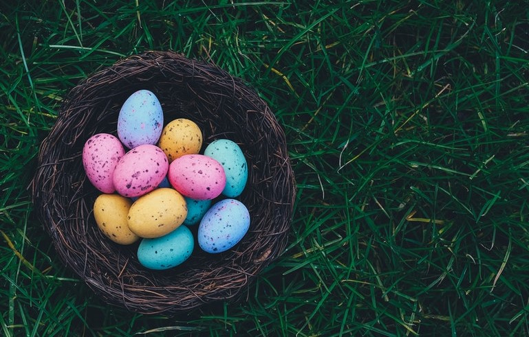 Photo of colored eggs in wicker basket.