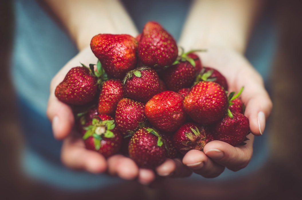 Photo of two hands holding strawberries.