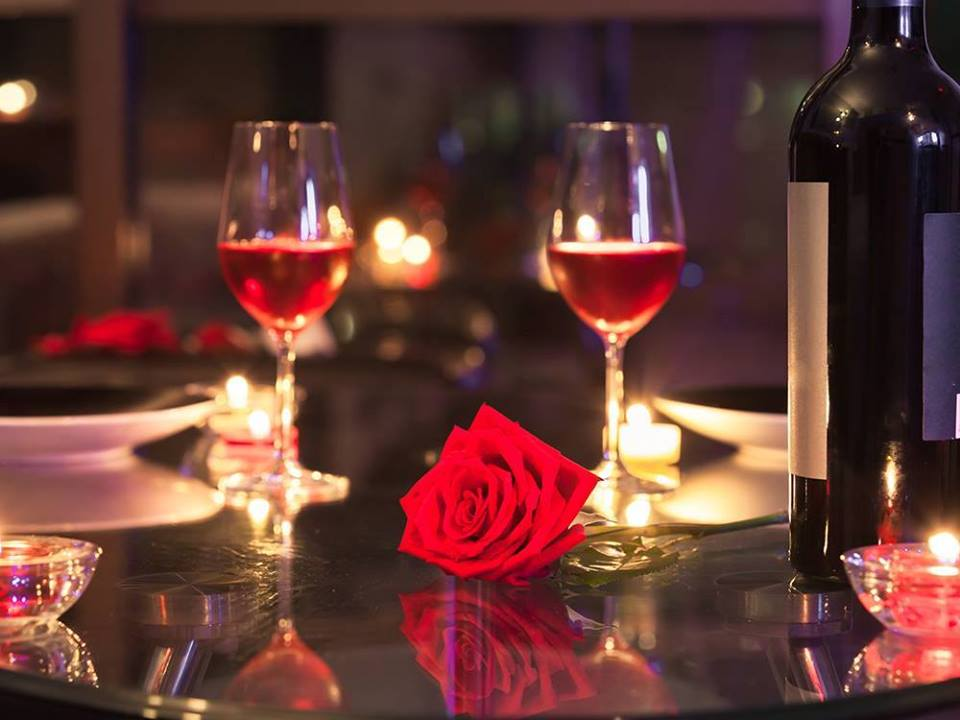 Photo of full wine glasses with a rose.