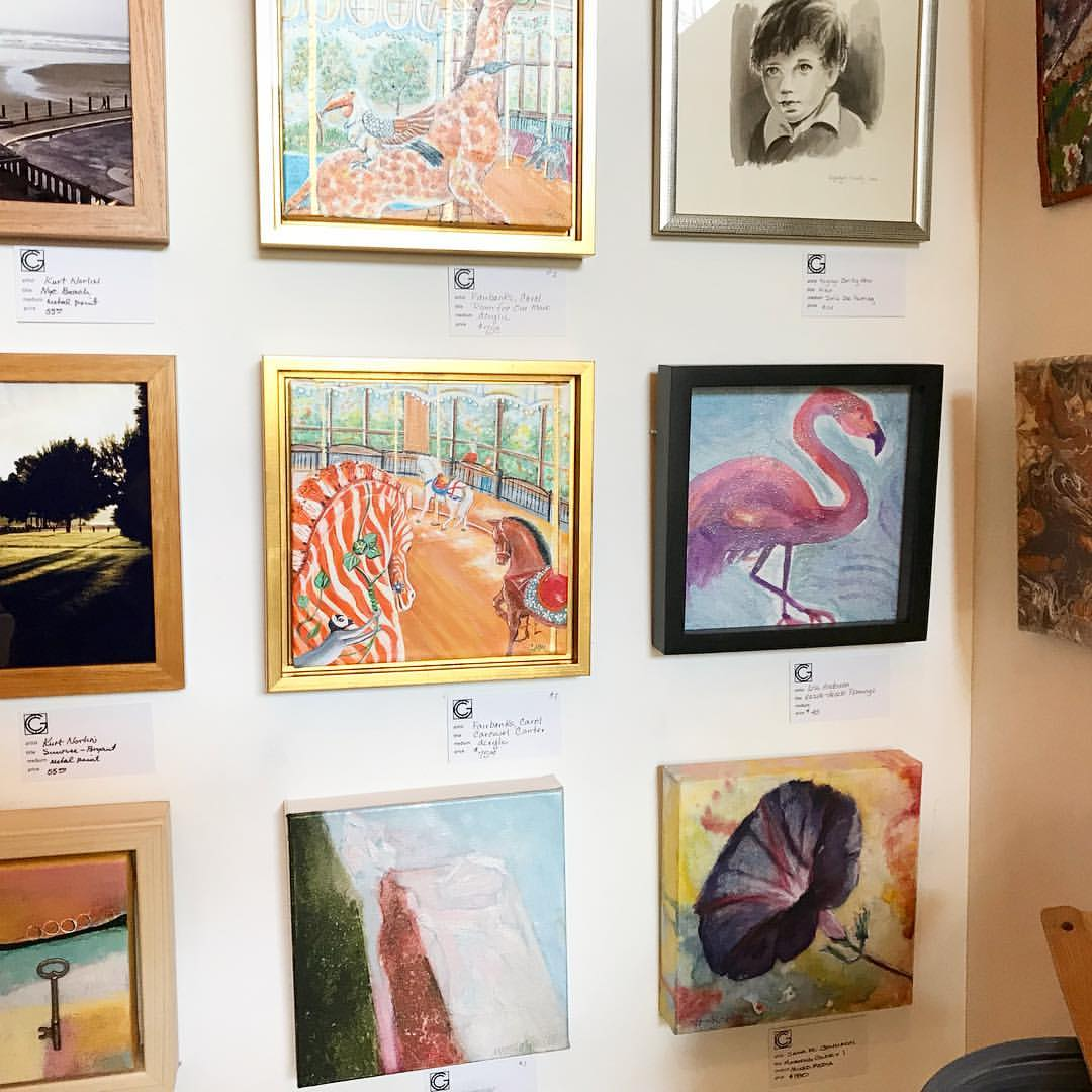 Photo of several small art pieces on wall.