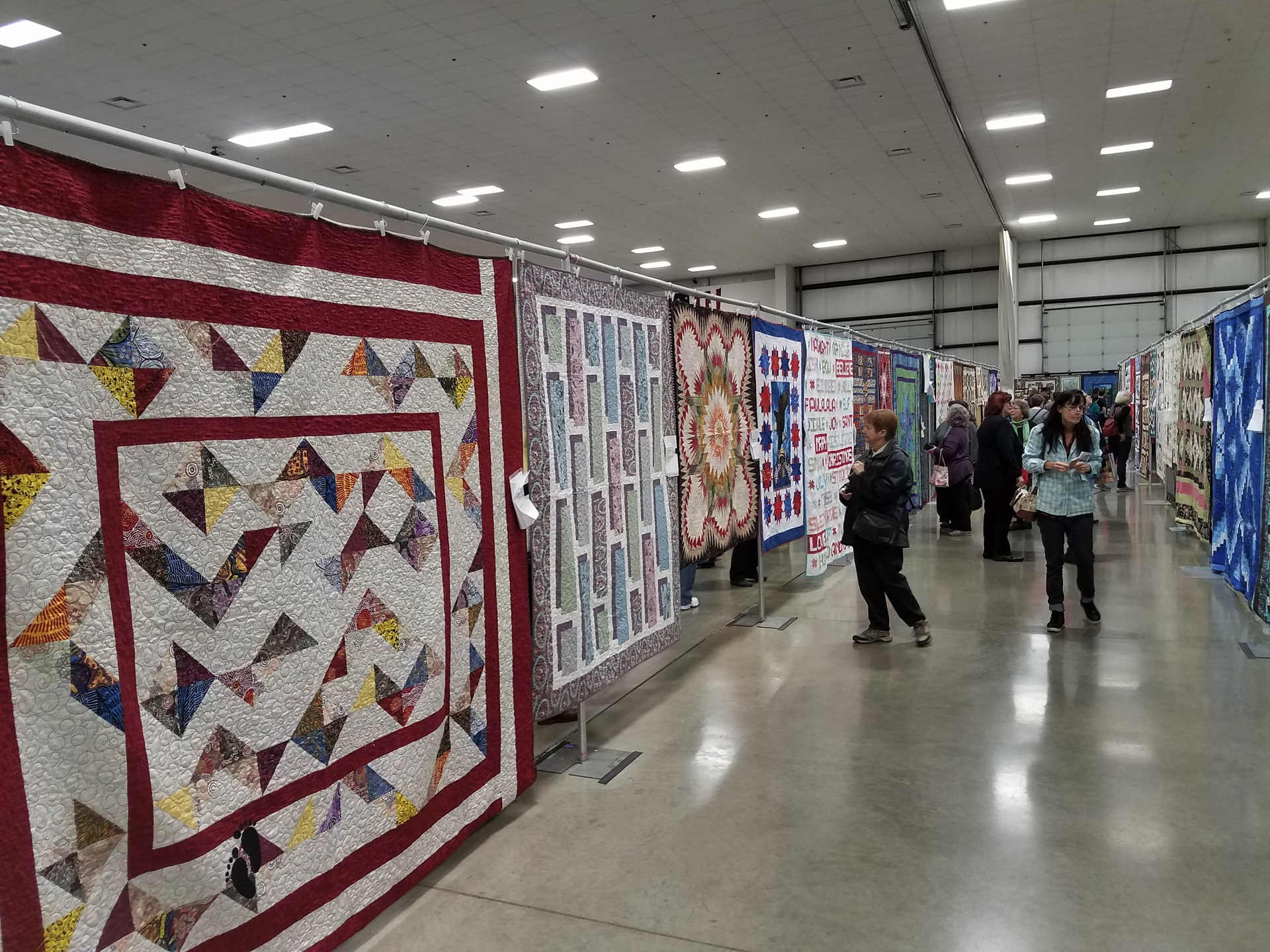 Photo of the first Willamette Valley Quilt Show in 2018, showing quilts hanging on display in the Linn County Fairgrounds exhibit hall.