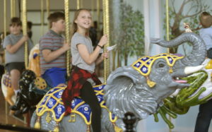 Photo of a pre-teen girl sitting on a hand carved wooden elephant on the Albany Historic Carousel