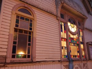 Photo of the historic Cumberland Church in Albany Oregon, close up of stained glass windows at dusk with light shining through them