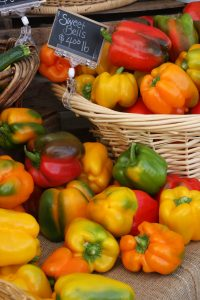 Photo of brightly colored bell peppers spilling out of a rattan basket at the Oregon Albany Farmers' Market