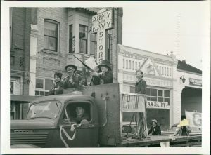 Vintage photo of downtown Albany Oregon and a parade in front of the old Dairy Building, now Novak's Hungarian Restaurant