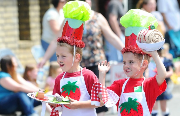 Photo of two young boys dressed in aprons and strawberry themed hats at the Lebanon Strawberry Festival parade in Linn County, Oregon.