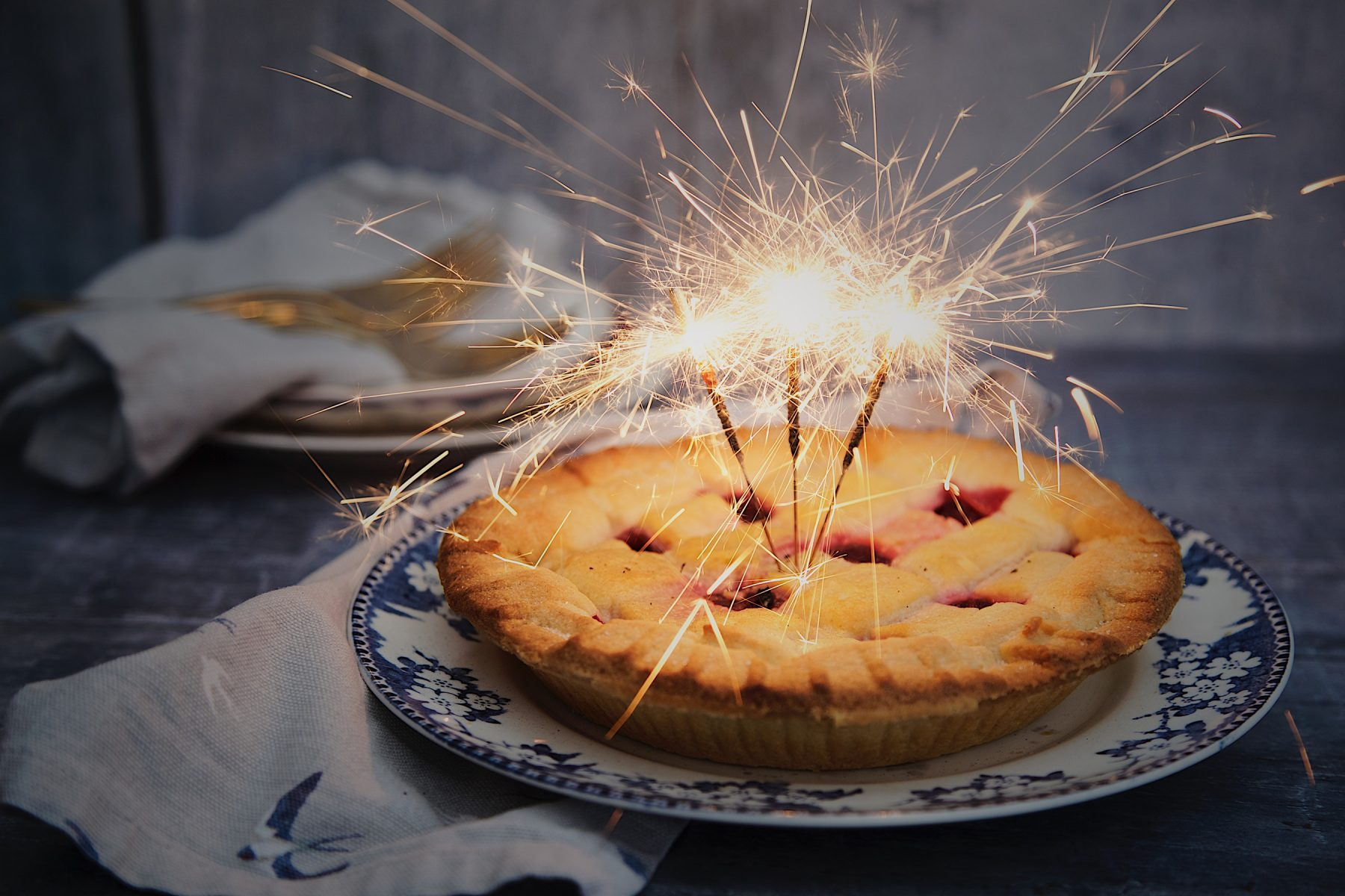 Photo montage of a berry pie with sparklers to celebrate Independence Day