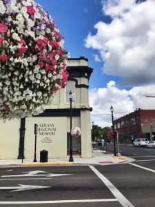photo of the Albany Regional Museum exterior with blue skies, big white clouds and hanging flower baskets