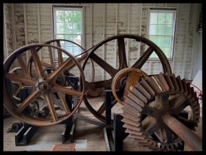Photo showing large gears and mechanisms that drive the water-powered Thompson's Mills