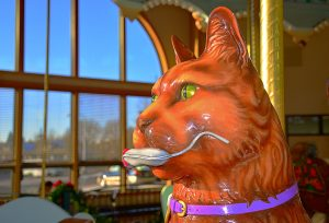 Photo of carved wooden carousel animal, a kitty, with a mouse in its mouth