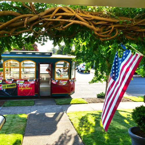 Photo of a historic home porch looking out to antique trolley and American flag during the Albany Sumer Historic Home Tour