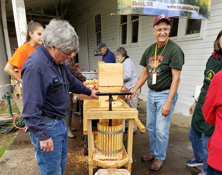 People pressing apples into cider.