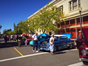 Photo of classic antique cars lined up in front of buildings in Downtown Albany Oregon. at the Antiques in the Street annual event