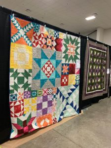 Photo of a a couple of quilts hanging up at the Willamette Valley Quilt Festival