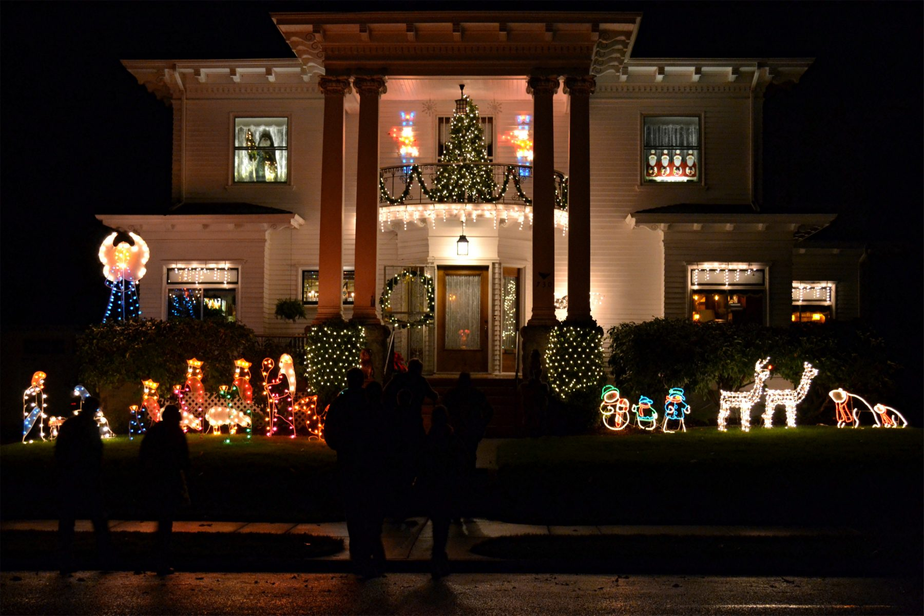 A historic home in Albany Oregon lit with Christmas lights and decorations on the exterior
