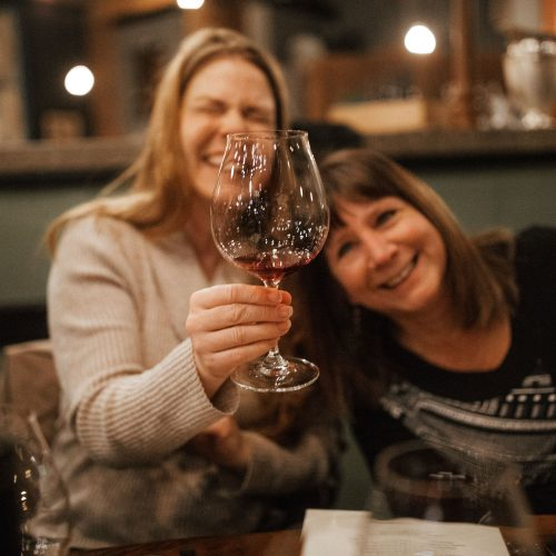 Photo of two women drinking wine and laughing at Sybaris Bistro in Albany Oregon