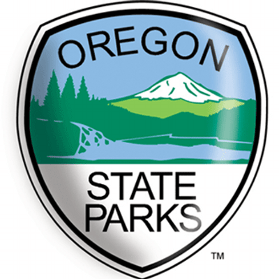 Graphic logo of the Oregon State Parks showing a snow covered mountain and a lake bordered by fir trees on a shield shape background