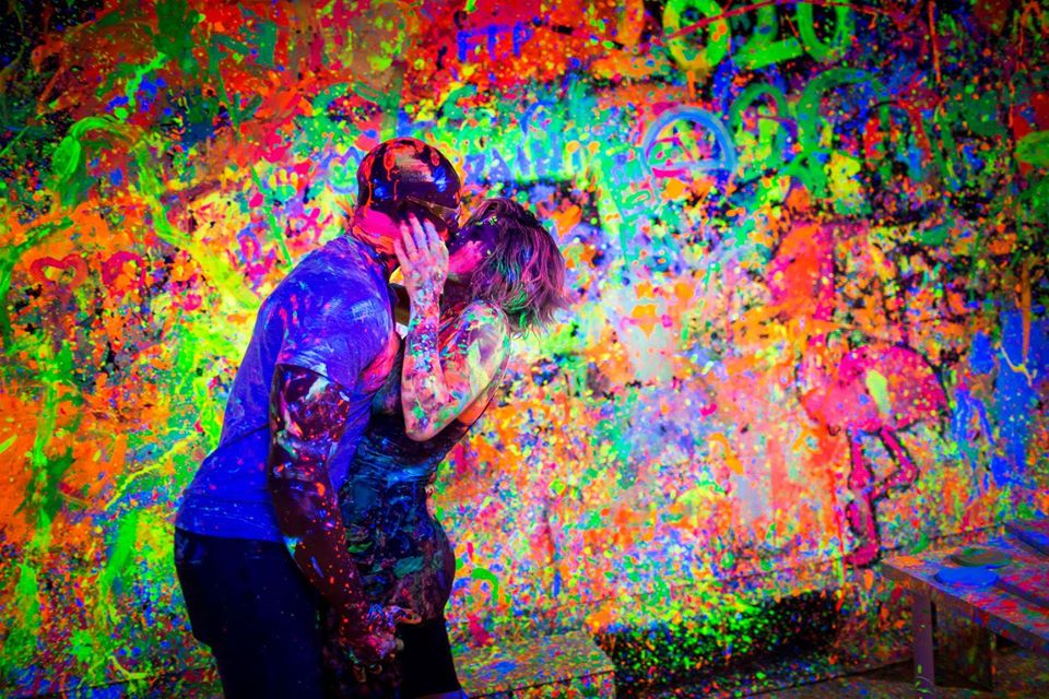 Photo of people covered in paint kissing.