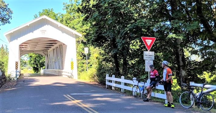photo of bikers in front of covered bridge