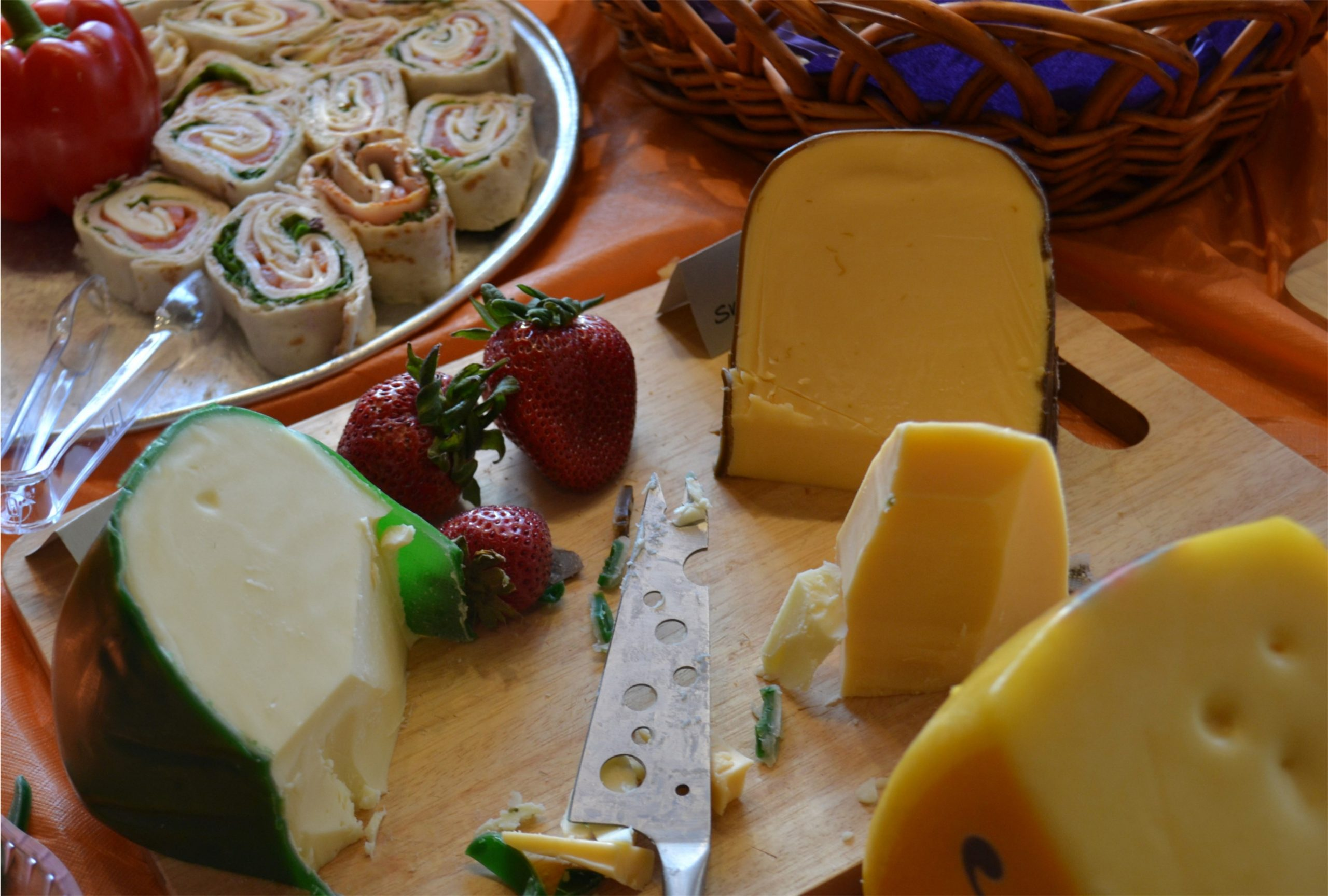 Photo of different cheeses on board with fruit.