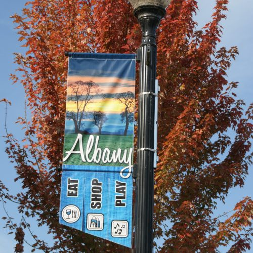 "Photo of banner in Historic Downtown Albany, OR, reads ""Eat, Shop, Play."""""