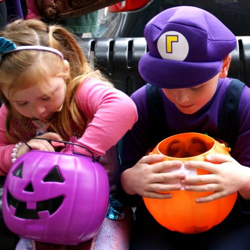 Photo of kids in Halloween costumes looking at candy.