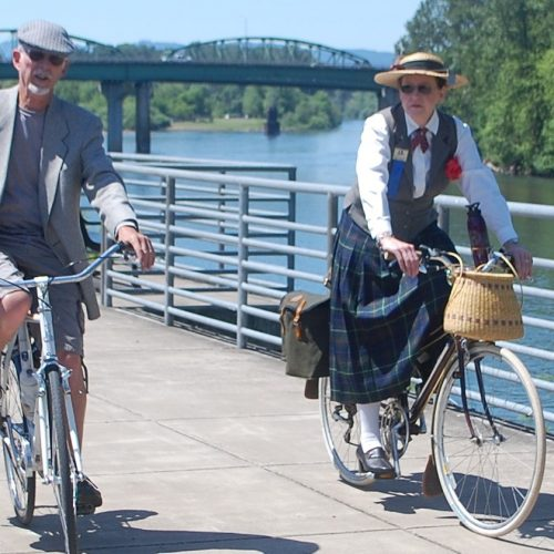 Photo of two people riding bicycles on path with river in background.