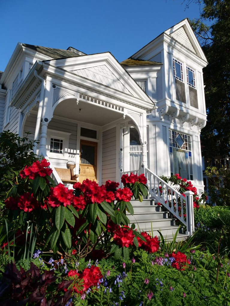 White hisstoric house with red flowers, Albany, OR Photo by Camron Settlemier