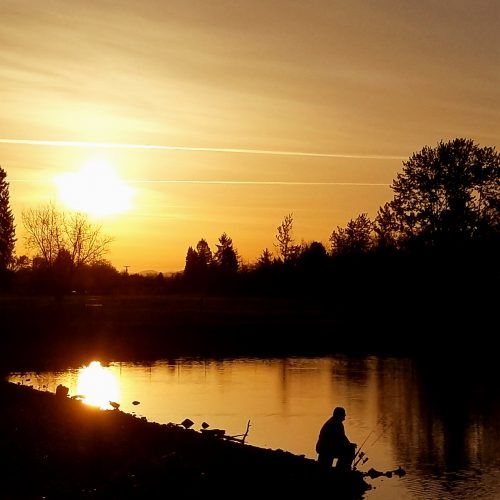 Photo of person fishing on river at sunrise