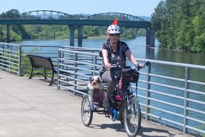 Photo of woman riding trike with dog along river path in summer
