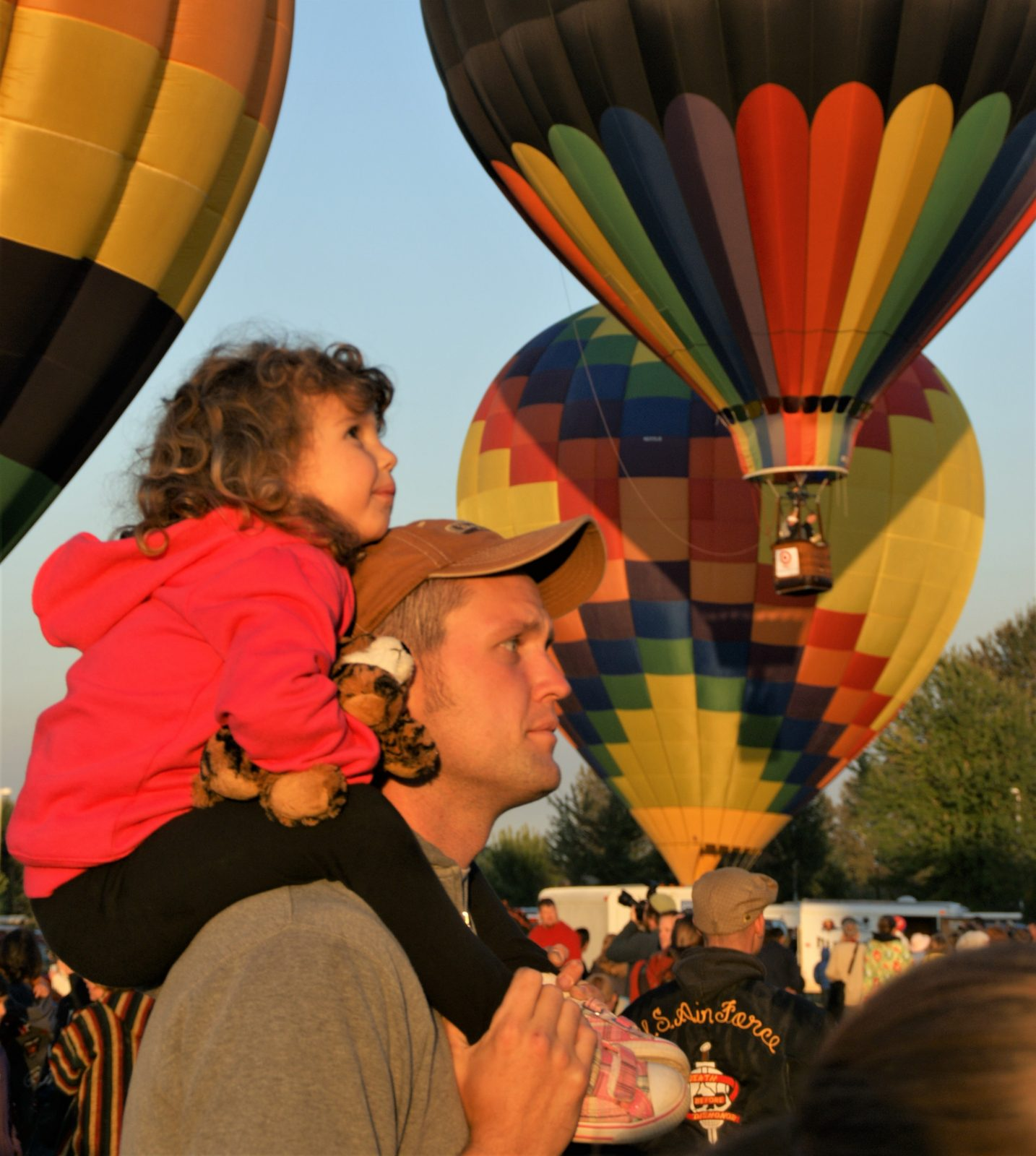 Photo little girl on man's shoulders hot air balloons in background